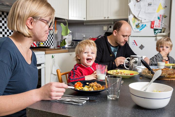 perhe on syömässä päivällistä ruokapöydän ääressä